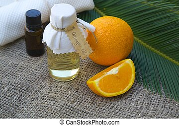 Bottle of orange oil. Fresh oranges in the background
