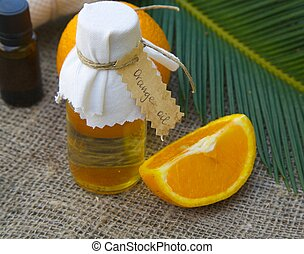 Bottle of orange oil and one fourth of an orange