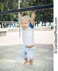Baby hanging on a pull-up bar