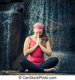 Sukhasana - Woman practicing yoga near waterfall Easy Pose...