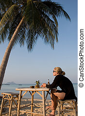 Woman sitting at table on tropical beach
