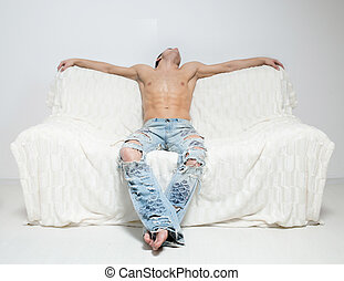 muscular man in torn jeans sitting on the sofa - muscular...