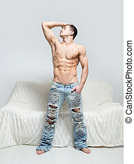 muscular man in torn jeans stands near the sofa - muscular...
