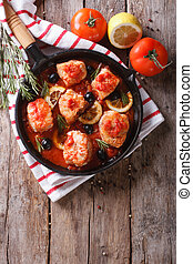 Pieces of fish in tomato sauce in a frying pan. vertical top...