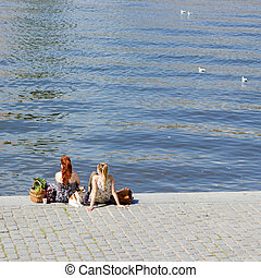 People sitting by the river - Two young girls and dog are...
