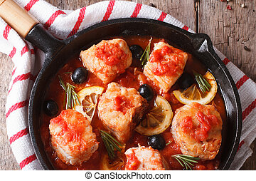 Fish fillet in tomato sauce in a pan closeup. horizontal top...