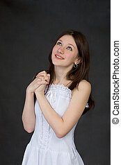 Pensive beautiful girl in white dress on black background