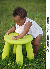 Toddler playing with chair - Adorable toddler playing with a...