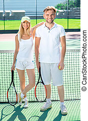 Young couple playing tennis - Young married couple playing...