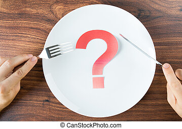 Plate With A Question Mark On Desk - Cutlery In Hand With...