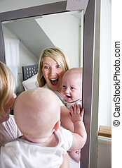 Mother and baby playing in mirror - Mother and 7 month old...