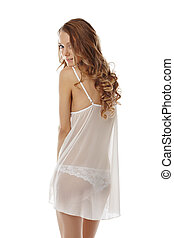 Flirtatious girl posing in sexy negligee, isolated on white