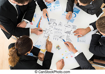 Group Of Businesspeople Analyzing Graph - High Angle View Of...