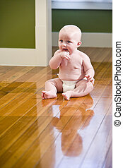 Chubby baby sitting on floor wearing diaper - Chubby seven...