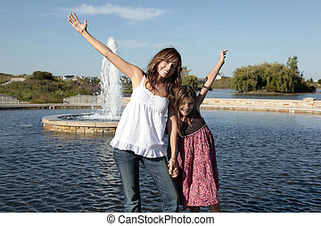 Mother and daughter with outstretched arms at fountain