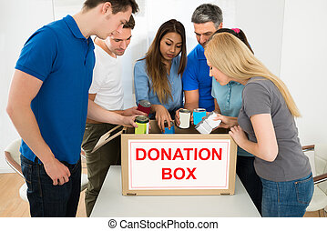 People Looking Inside Donation Box - Group Of Multiethnic...