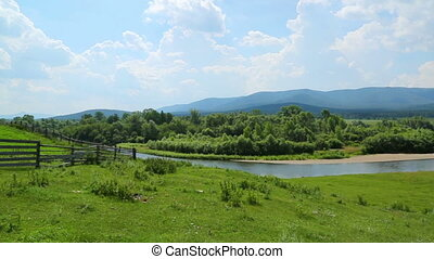 panorama landscape with river between mountains and horses -...