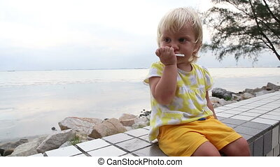 little blonde child eats biscuits at seafront - little...
