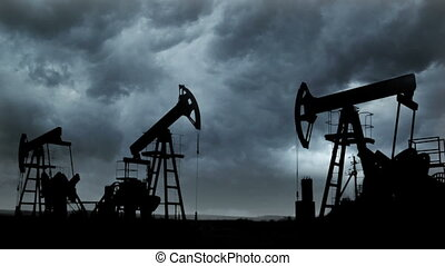 working oil pumps silhouette against background of storm clouds