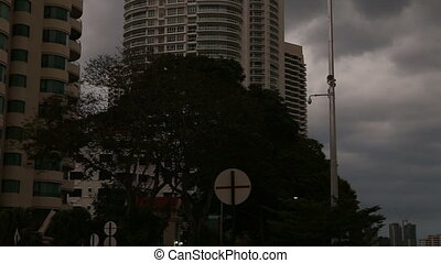 skyscrapers under grey sky and dark clouds - city view of...