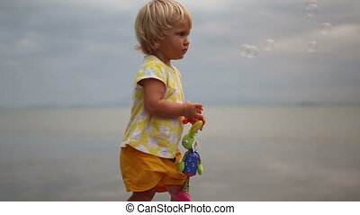 little blonde child comes up to mother blowing soap bubbles...