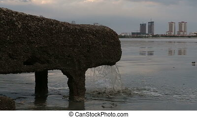 pipe of sewer water from sewerage system directly near sea...
