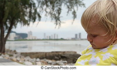 mother gives blonde daughter biscuits to eat at seafront -...