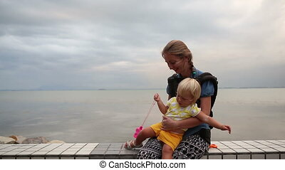 blonde child gets down from mothers arms at city seafront -...