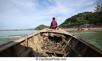 boy sits on longtail boat sailing out beach in tropics -...