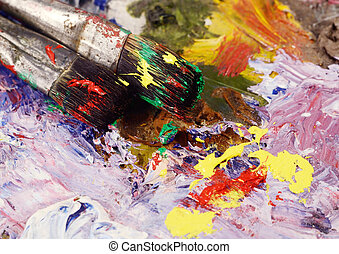 Art still life - two paintbrushes and dirty palette with colour