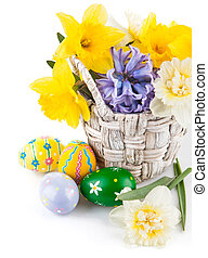 Easter eggs with spring flowers in basket Isolated on white...