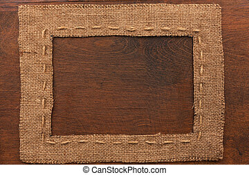 Frame of burlap, lies on a background of wood, with place...
