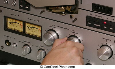 hand man operates reel tape recorder