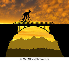 Cyclist riding across the bridge at sunset