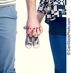 Future parents holding hands and a pair of little shoes over...