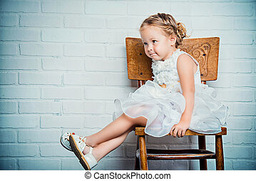 sitting on chair - Sweet little girl in a beautiful white...