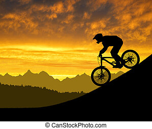 silhouette of the cyclist on downhill bike at sunset