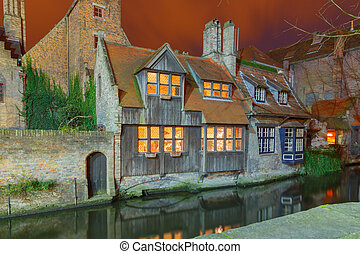 Bruges. Old, stone, medieval house on the canal at night.