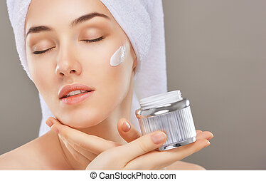 applying cosmetic cream - beautiful woman applying cosmetic...