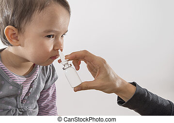 parent's hand of a girl applies a nasal spray