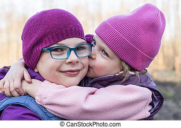 sister lovingly kissing her older sister - Younger sister...