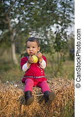 Little girl eating a pear