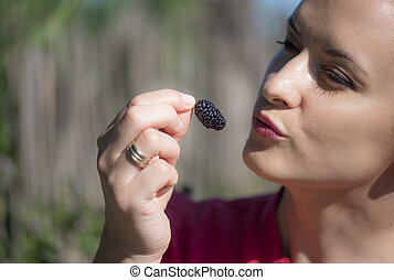 Beautiful woman eating a mulberry