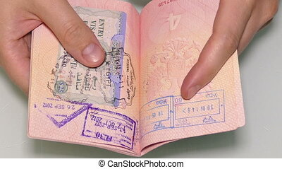 man's hands turning the pages of the passport with visas and...
