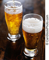 two mugs of amber beer with foam head