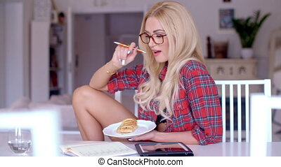 Woman enjoying a snack while working at home - Attractive...