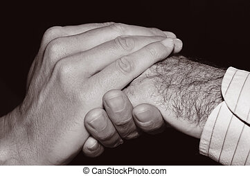 young man holding the hand of an old man, in black and white...