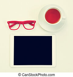 eyeglasses, tablet computer and cup of tea