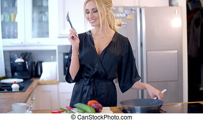 Sexy blond housewife cooking dinner standing at the counter...