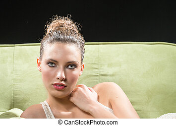 Beautiful girl laying down on a green sofa